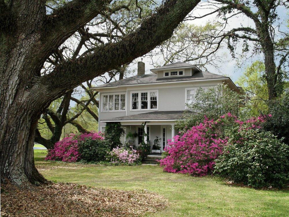 Large rural setting foursquare home with partial porch.