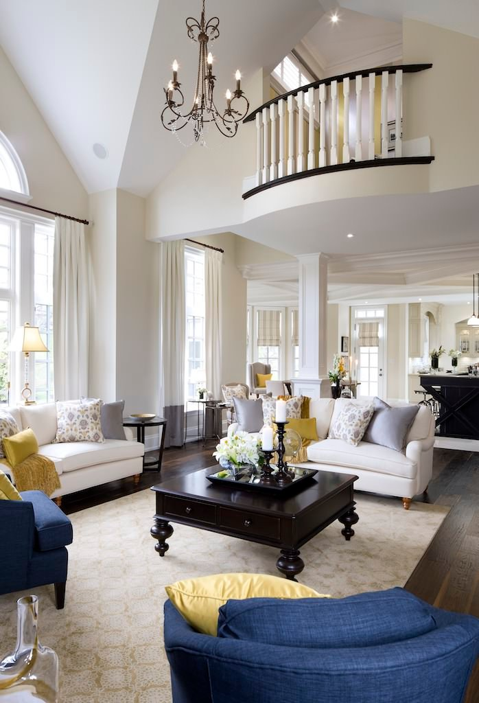 This living room is delicately touched up with white walls stretching along the second level and the cathedral ceiling. The white sofa is paired up with blue chairs and some wooden furniture that clicks with the wooden floor.