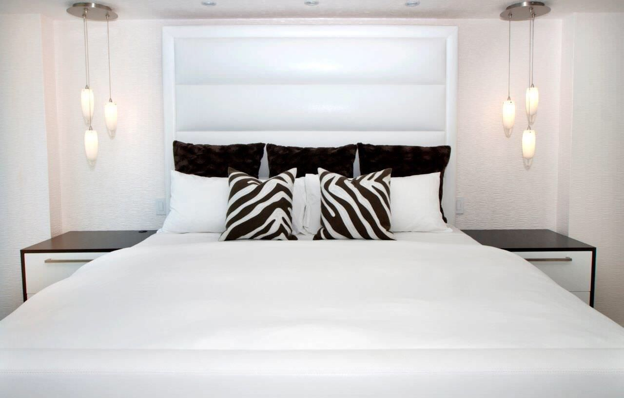 All white primary bedrooms can give the illusion of looking larger than they are.