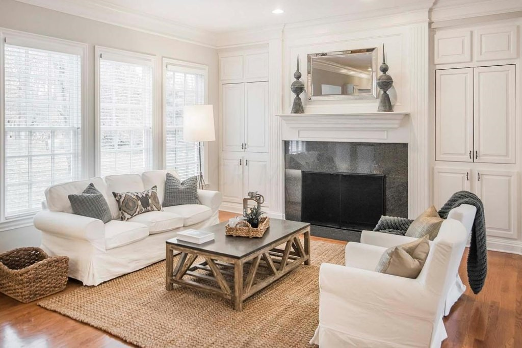 This is a simple rustic living room decorated with a basket, floor rug and rough framed center table inspired by native handicrafts. The white covered sofa set matches the white ceiling and walls.