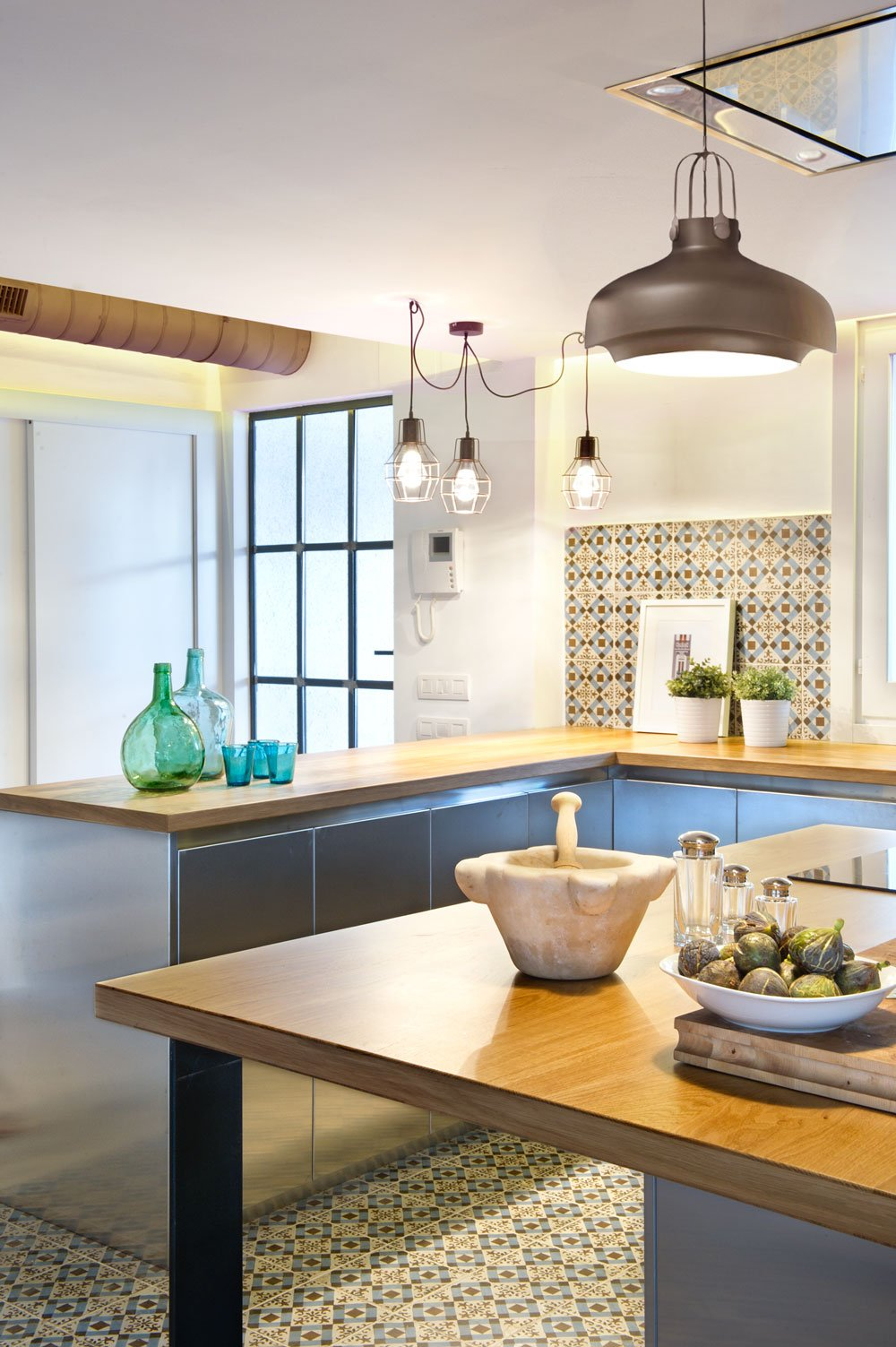 With these extra bright pendant lamps, the beauty of this kitchen is made even more visible. As you can see, the ornate tile patterns, wood top and steel cabinets are wonderfully present.