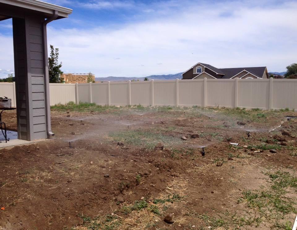 DIY backyard timer-based sprinkler system sprinkling the yard