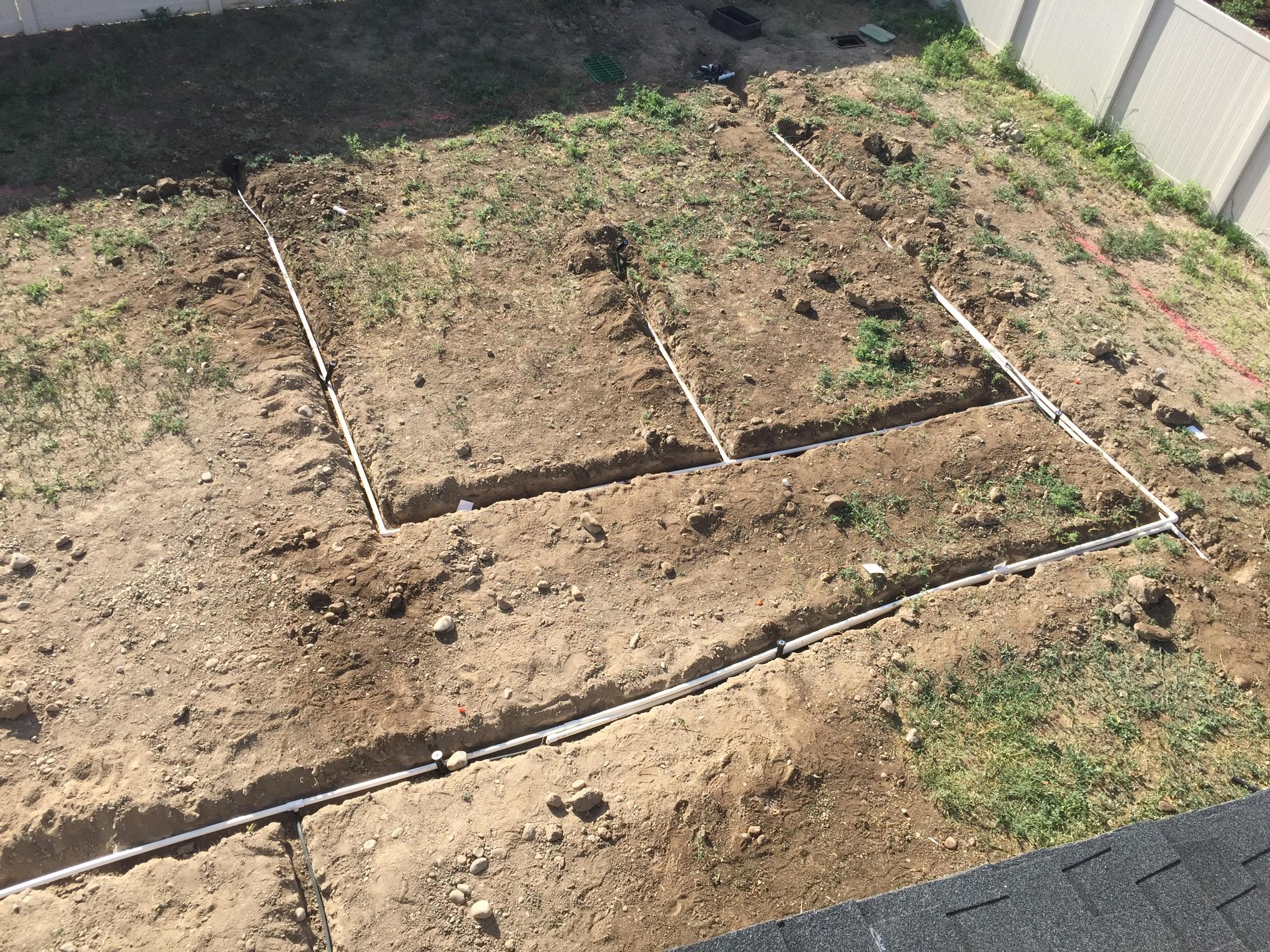 Installing sprinkler pipes underground for backyard sprinkler system