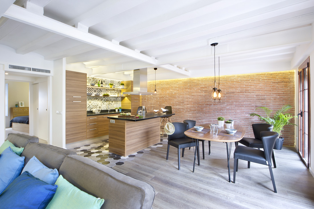 The open concept of this design is quite stunning in its linking dining area and mini bar/kitchen. The shades of grey on the flooring add to the industrial look.