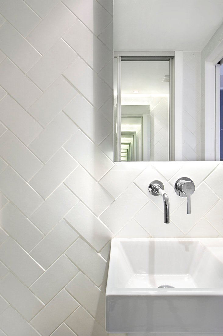 White tile in herringbone laying pattern, a sink and a faucet complete the functional and nice set up of this bathroom. Add up the mirror that creates a wider illusion on the space.