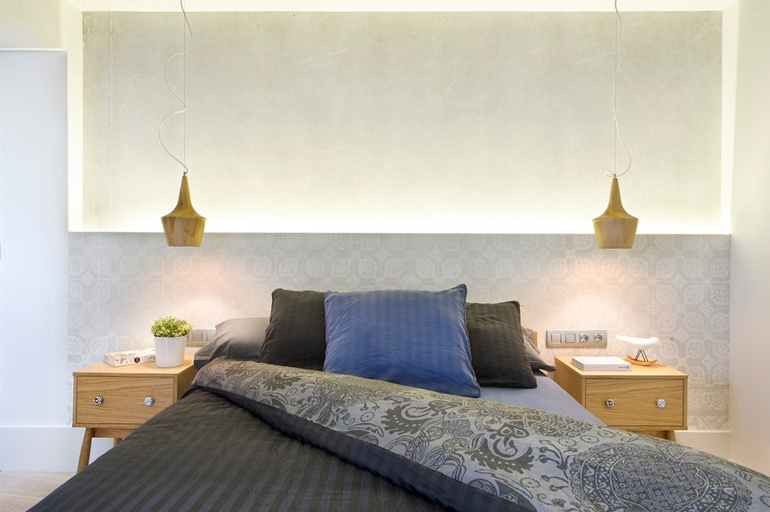 Symmetrical plugs, desks, and ceiling lights hovering on the ceiling. The extra lighting are provided behind the patterned wall that also serves as the artsy headboard.
