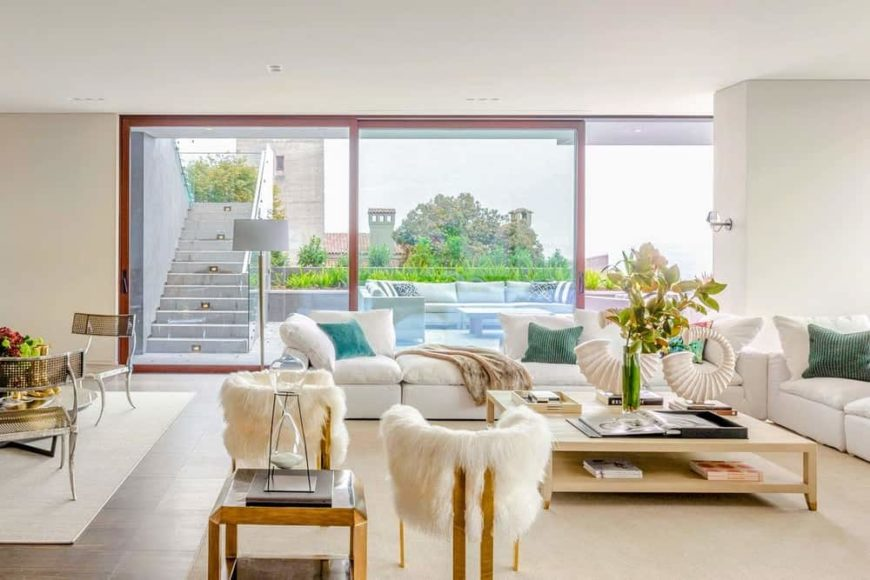 The bright living room has an abundance of natural lighting thanks to the wide glass windows with sliding glass doors augmented by the bright wall tones.