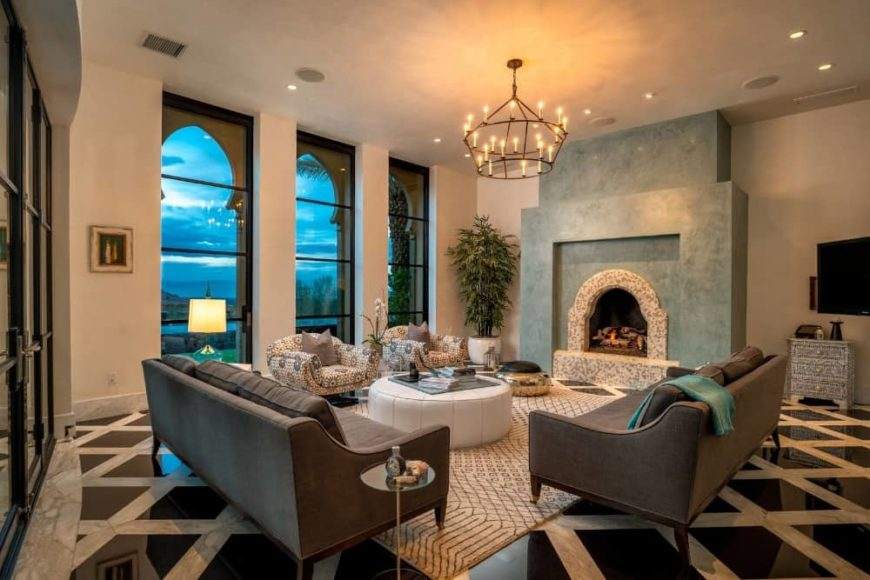 This living room features a comfy sofa set and a circular table on the rug. This living space brightens by dazzling chandelier and it also has a fireplace.