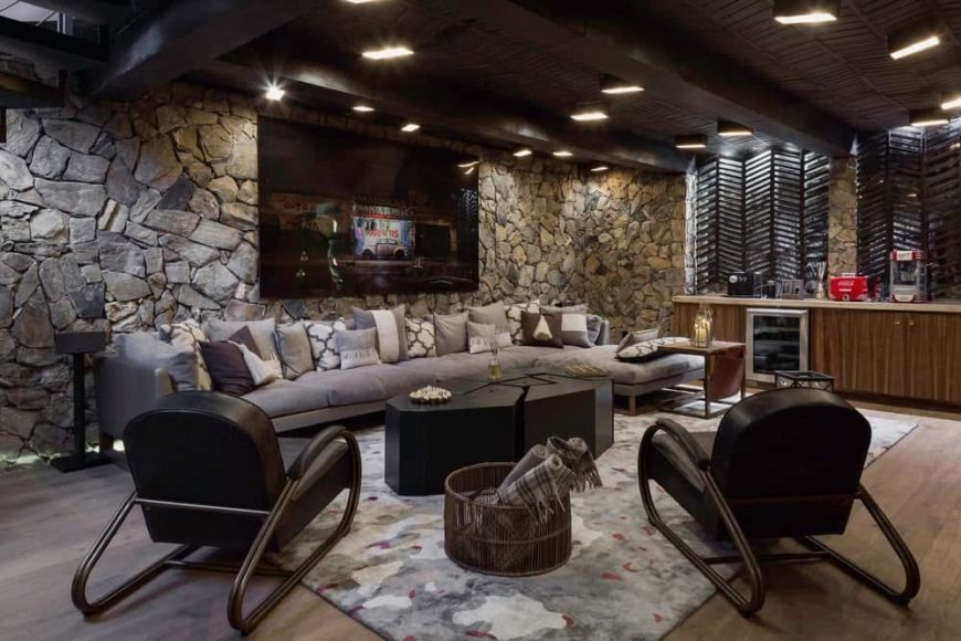 This basement is fitted with a relaxing L-shaped sectional sofa that balances the harsh texture of the stone wall behind it that is adorned with large wall-mounted artwork.