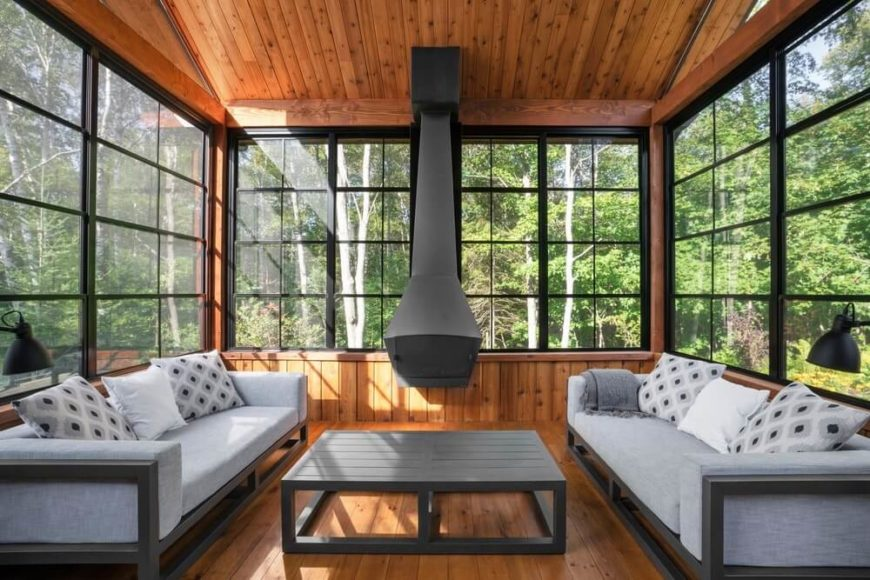 This living room features a grey sofa set with a square table in the middle. It also has hardwood flooring and windows with a great view of the forest.