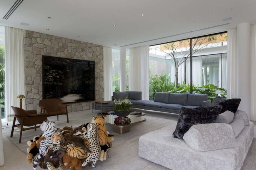 The large and airy living room has an abundance of natural lighting due to the large glass walls on two sides that afford nice views of the landscaping outside.