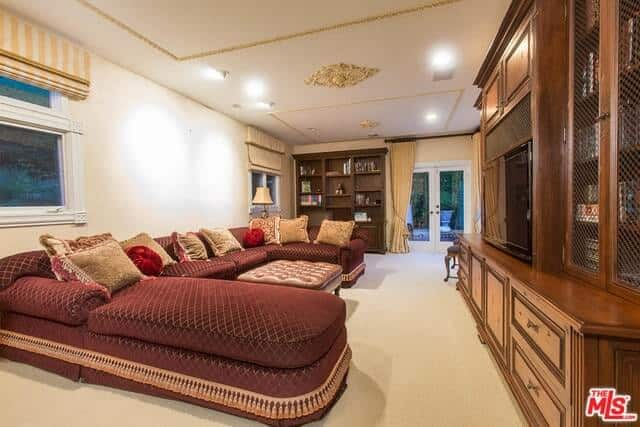 This living room presents a U-shape cozy sofa set with a leather table in the middle. It also has wooden cabinetry and a TV on top of the cabinet.