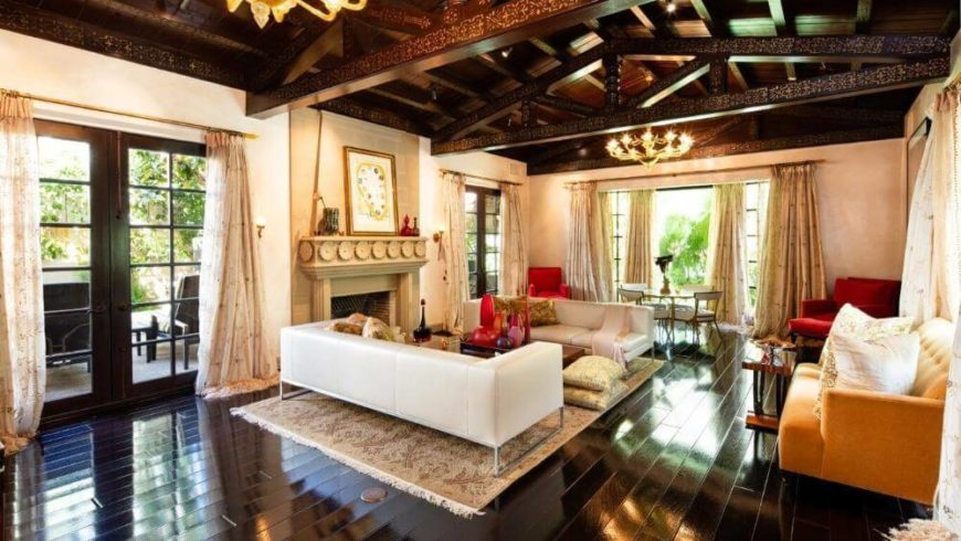 Large formal living room with well-polished hardwood flooring and a wooden ceiling with exposed beams.