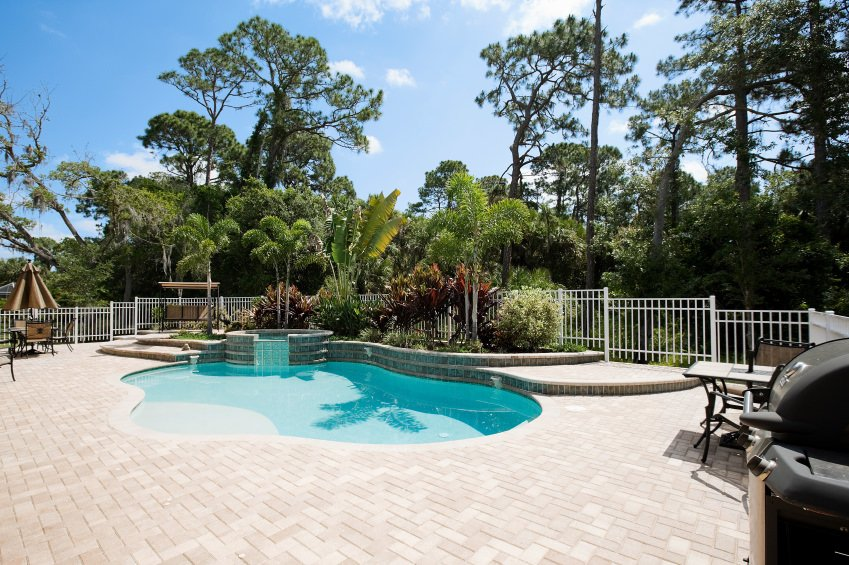 I love the massive brick patio surrounding this small kidney shaped swimming pool. There's also a nice garden wrapping around part of the pool.