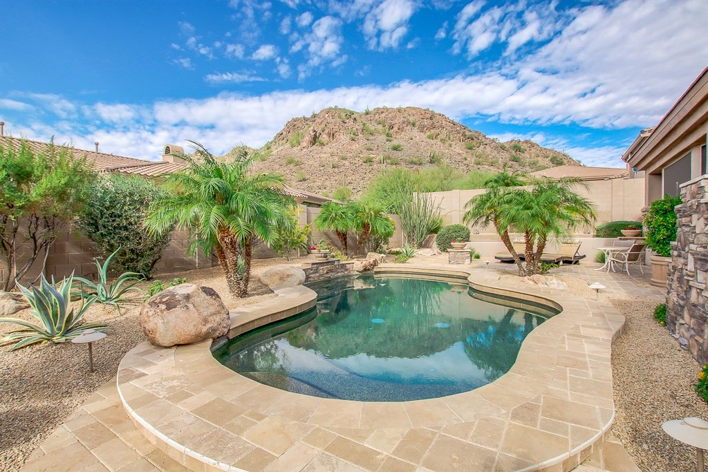 Small kidney-shaped pool in the backyard of a desert suburban home. It's a small backyard but looks fabulous with the small pool and and trees.