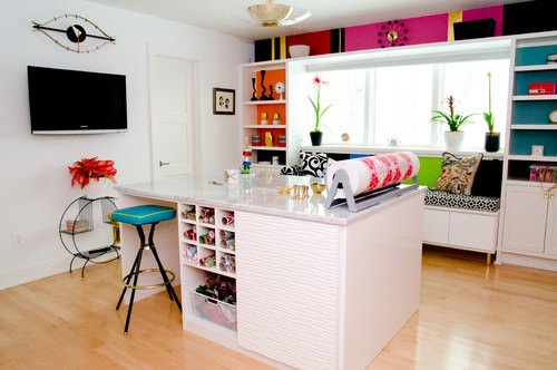 Colorful Craft Room with Island Work Station and Light Hardwood Flooring.