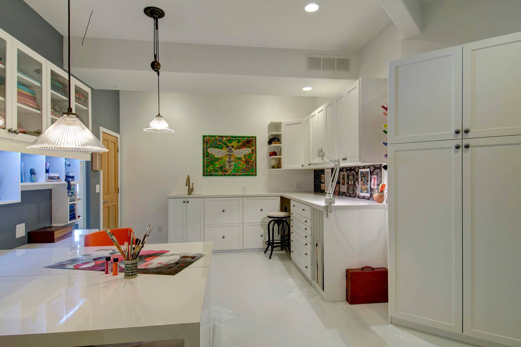 spacious white craft room with custom white cabinetry and multiple work stations - Custom Rooms