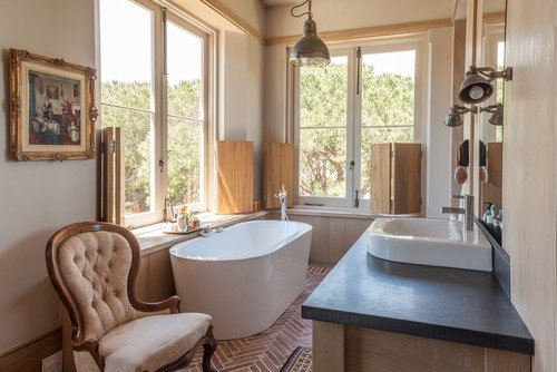 Transitional bathroom that has white freestanding tub and matching sink. / Photo by Wynand Wilsenach Architects