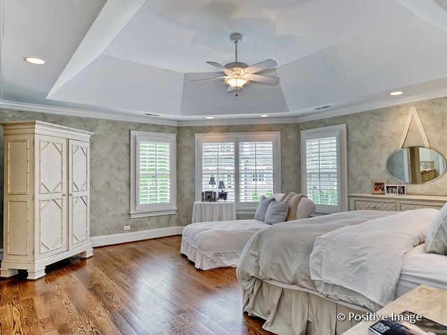 Spacious primary bedroom featuring stylish gray walls and a stunning tray ceiling lighted by recessed lights. The room also features hardwood floors.