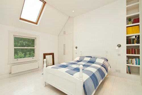 This master bedroom whitewashed from the floor to the ceiling creates a seamless flow that makes the blue-striped bedding seem afloat. Photo by Chris Snook