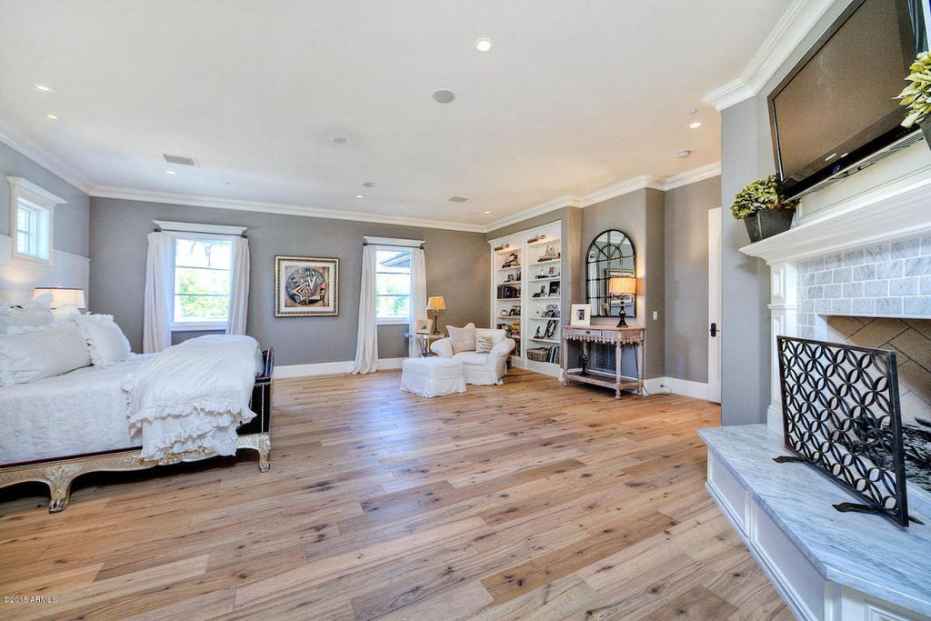 light wooden flooring steals the show for this spacious master bedroom