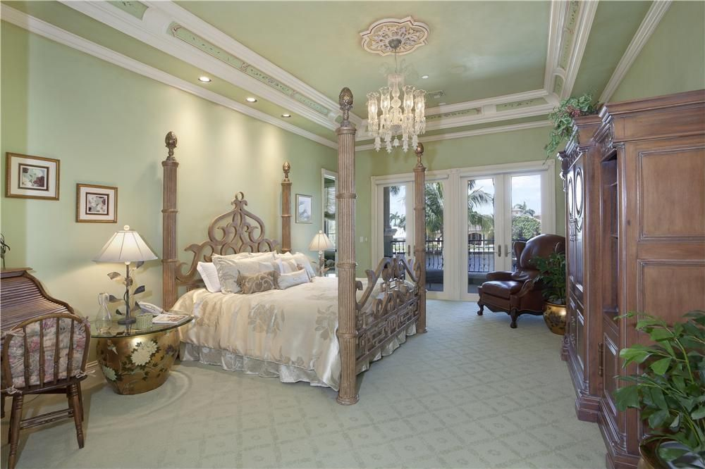 A primary bedroom with a luxurious bed set on the classy carpet floors and lighted by a glamorous chandelier set on the stunning tray ceiling.