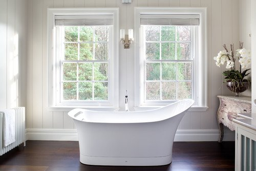 A transitional white bathroom with dark wooden flooring, freestanding tub and twin panel windows. / Photo by Paul Craig Photography