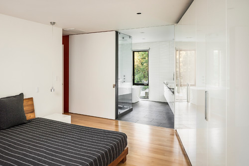 A glossy white exterior, clean straight lines and flat paneled cabinets make this contemporary master bedroom oozing with masculine and stylish appeal. Photo by RUFproject