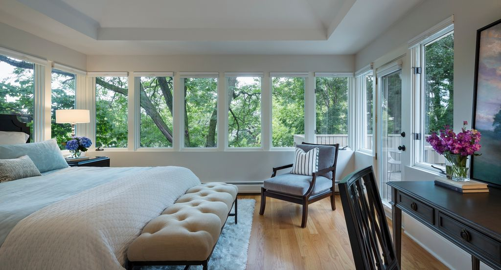 This master bedroom makes the nature scene outdoors as its focal points with its surrounding windows.