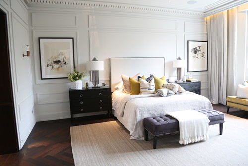 This master bedroom accentuates its high ceiling with white accents and molding details on the walls.Photo by Permanex Building Services