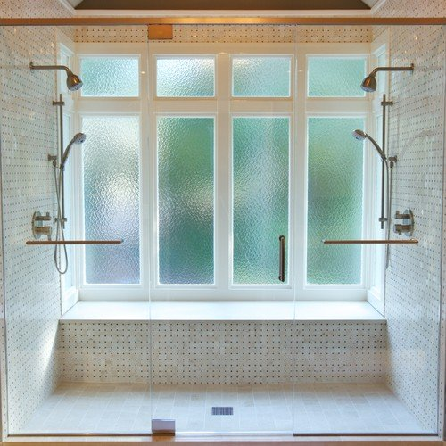 This transitional bathroom has mini marble tiles, a bench and two shower heads in an enclosed space. / Photo by Addhouse