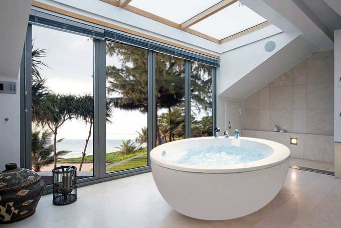 This spacious and relaxing bathroom is made more beutiful with the floor to ceiling windows that allow natural light to pass through.