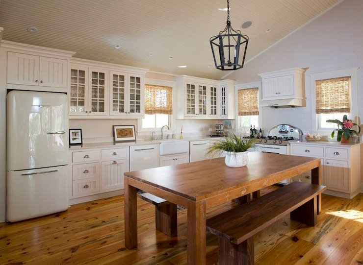 This white kitchen with vaulted ceiling looks spacious.