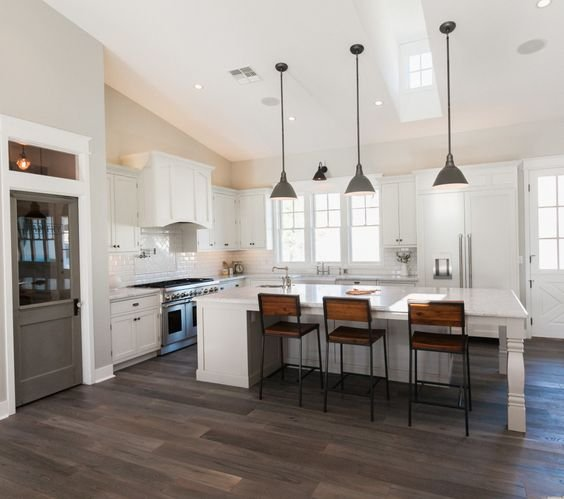 This spacious white kitchen looked even larger because of the white vaulted ceiling.