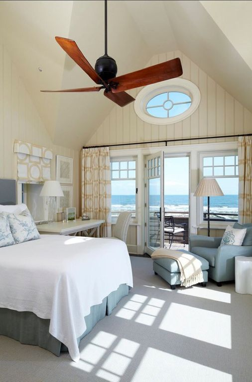 Small master bedroom featuring gray carpet flooring and a tall ceiling. There's a doorway leading to the home's deck overlooking the magnificent view of the surrounding.
