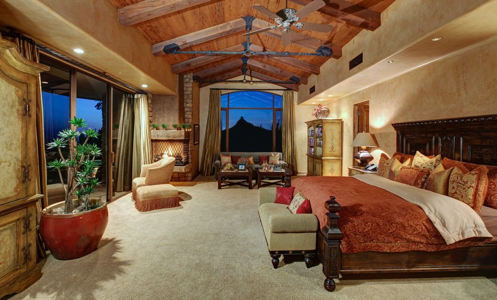 This large master bedroom offers a large bed set on the carpet floors. The room also features a tall ceiling with rustic beams.