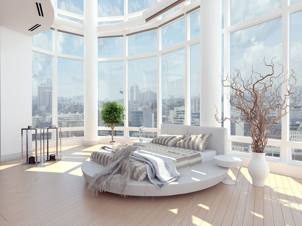 A huge primary bedroom with a charming white bed set on the room's hardwood floors. Glass windows surround the room overlooking the stunning city view.