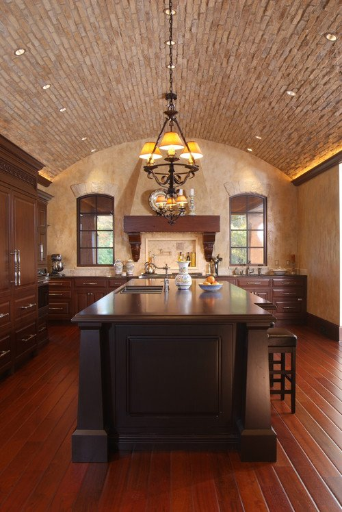 Timeless and traditional, this Tuscan kitchen features limestone accents, clay tile roof, arched windows, and Roman arches.