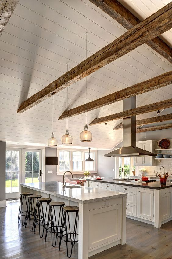 This white kitchen looked larger with the vaulted ceiling with exposed beams.