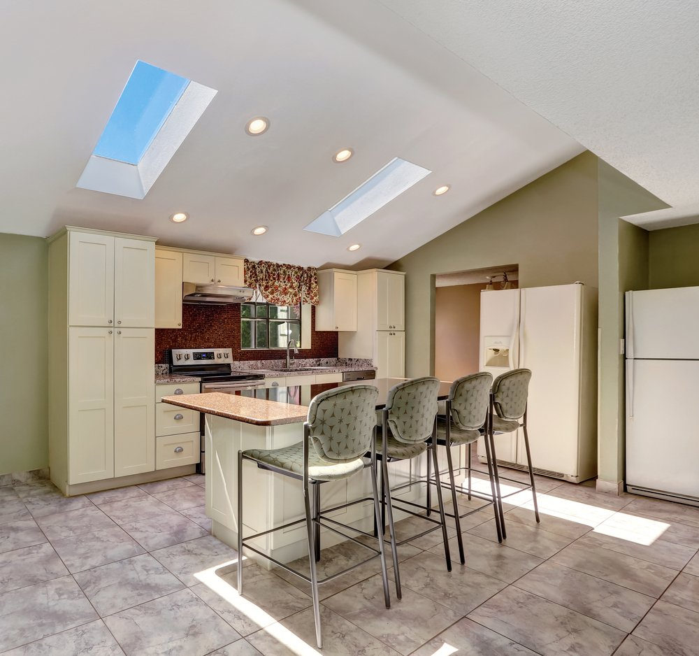 Minimal lighting is required in this vaulted ceiling kitchen with glass sky windows.