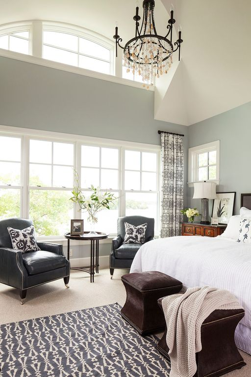 This master bedroom offers a large bed and a sitting area with a coffee table on the center. The room is lighted by a glamorous chandelier.