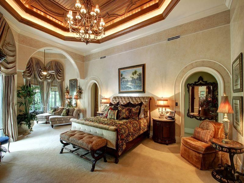 A luxurious primary bedroom featuring carpet floors and a stunning tray ceiling lighted by a glamorous chandelier.