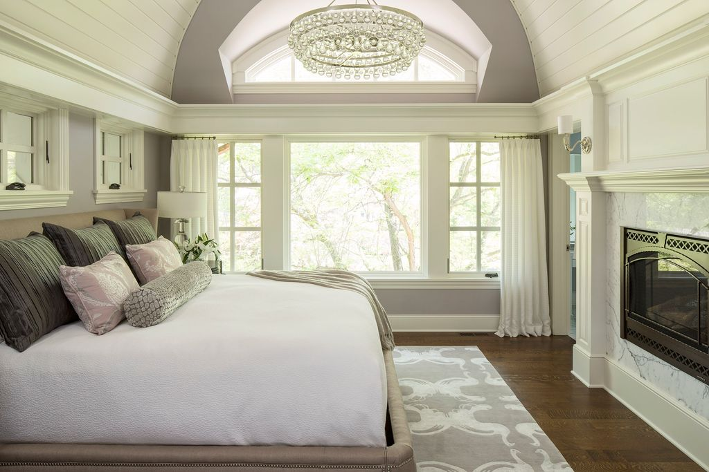 This master bedroom offers a large bed with a fireplace in front of it. There's hardwood floors topped by a rug. The room is lighted by a glamorous ceiling lighting.