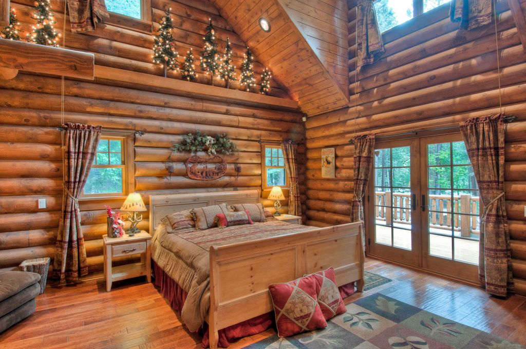 This primary bedroom is made of hardwood floors and thick logs. The room has a tall ceiling.