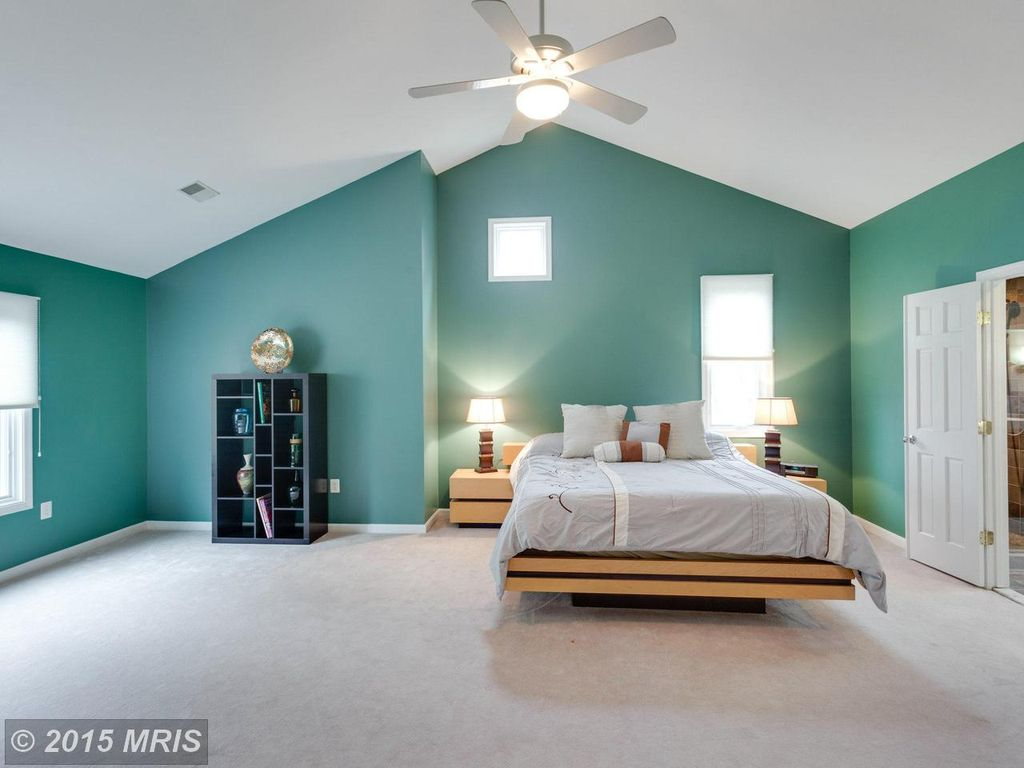 Large master bedroom with green walls and white carpet floors matching the white ceiling.