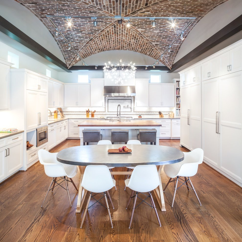 Winter white wall lined with white cabinets , paired with a grey dining table and white chairs complement each other in this vaulted-ceiling kitchen.