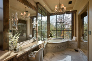 An era style bathroom with corner tub for long soaking and a wide clear 6 panel glass window that provides relaxing view of the outside greenery.
