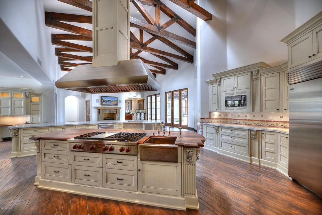 Exposed beams add visual interest to this already spacious kitchen with vaulted ceiling.