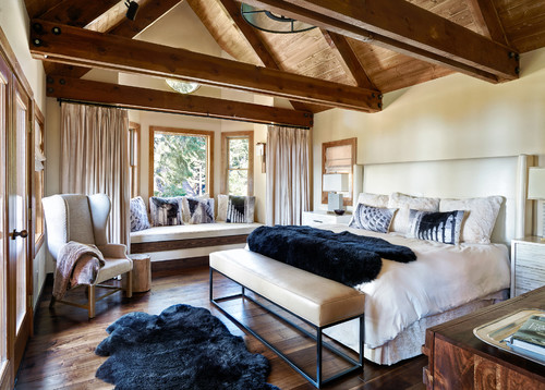The low rafters that expose this master bedroom's high ceiling matches with the dark wood flooring to create a rustic look. Photo by Sierra Sustainable Builders