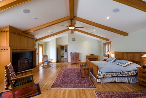 Warm tones on the exposed beams, flooring and wooden fixtures fill up this master bedroom for a cozy effect. Photo by Mostad Construction,Inc